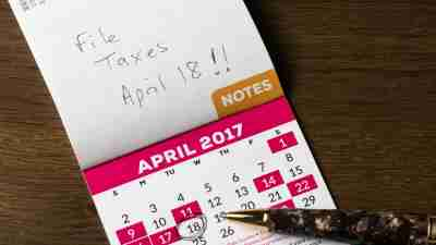 Gold pen laying on calendar belonging to ADHD person for tax day