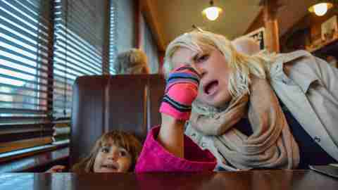 Little ADHD girl puts her socked foot on the table at a restaurant, her mother looks on in horror