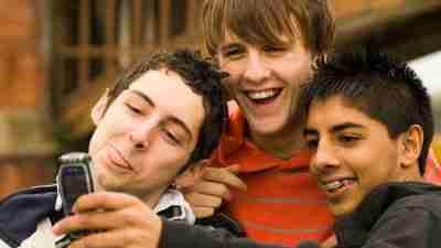 Close-up of three ADHD teenage boys taking a photograph of themselves with a mobile phone
