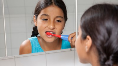 Child with ADHD brushing her teeth trying to avoid the morning rush