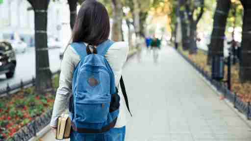 A college student walks outdoors and thinks about college accommodations