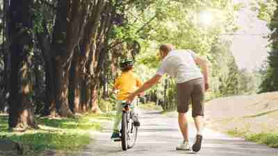 Father help his ADHD son ride a bicycle