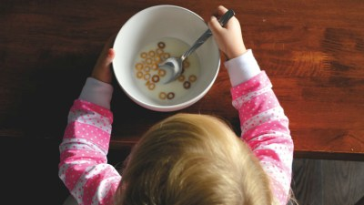 girl with adhd eating a bowl of cereal as part of her morning routine