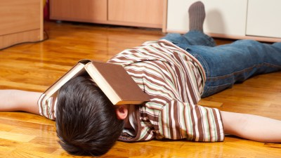 Boy lying on the floor with a book over his face to escape his homework problems