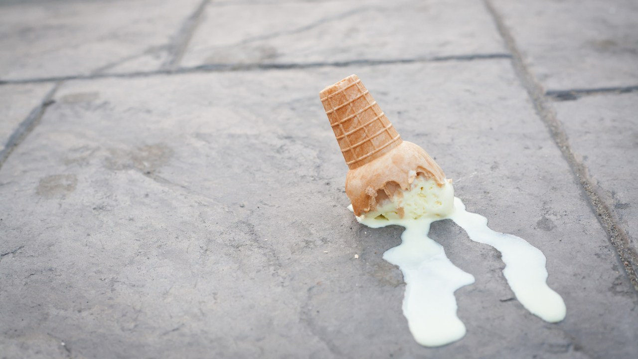 An ice cream cone dropped on the ground by a clumsy child