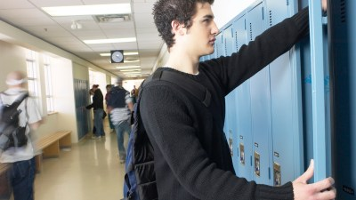 A teenager getting things out of his locker to help him manage his behavior in the classroom