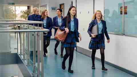 Teen girls walking down a school hallway