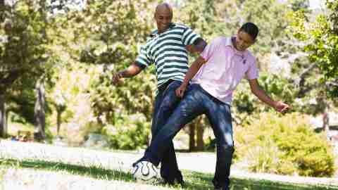 A father parenting his teenager by playing a fun game of soccer