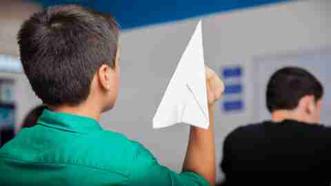 A boy throws a paper airplane in class without realizing it's part of the connection between ADHD and behavior.