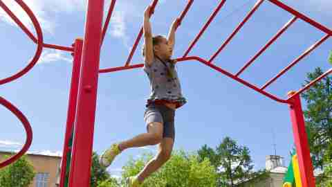 An impulsive little girl on a jungle gym