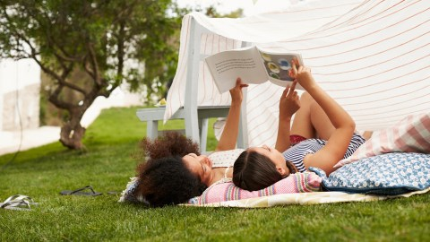 A mom reads outside with her daughter with ADHD to help improve her behavior