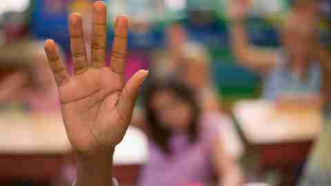 A student raises her hand in class, something that is hard for kids with ADHD and behavioral impulsivity.