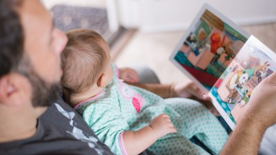 A man reads with a child, one part of his mission to be a better dad.