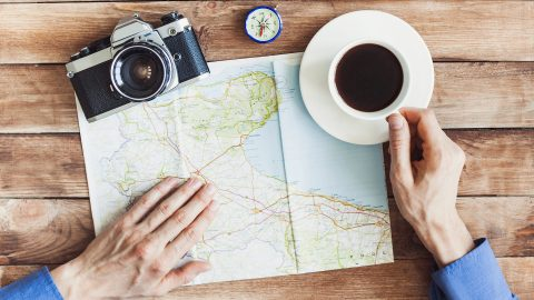 A man with a map and a cup of coffee listening to one of the best ADHD podcasts