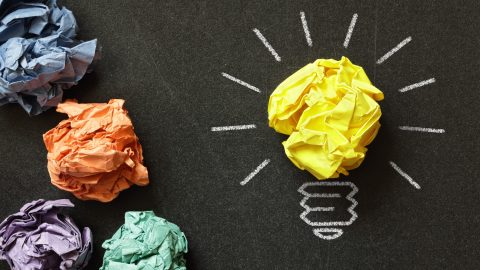 Paper lightbulbs representing productivity concepts in one of the best ADHD prodcasts