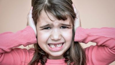 An explosive child dealing with her anger by crying and putting her hands on her head
