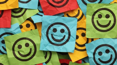 Colorful crumpled adhesive notes with smiling faces. that symbolize emotional regulation