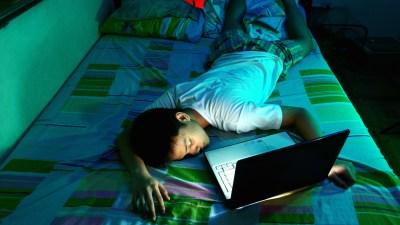 A teen who has trouble sleeping laying in front of his open laptop on his bed
