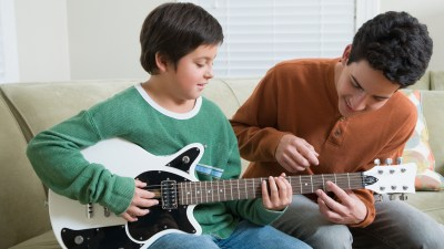 An older brother teaching his younger brother how to play guitar to learn responsibility