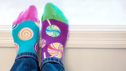 A pair of mismatched socks on child's feet, defying a common societal expectation of mothers