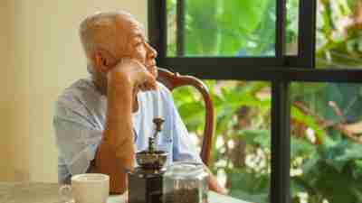A senior man with ADHD, staring quietly out the window of his home