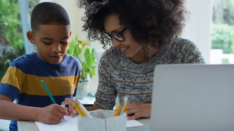 Mother helping his son in doing homework at home 4k