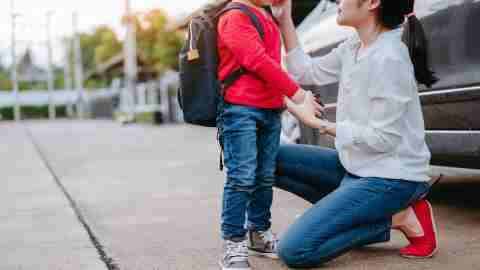 An ADHD mom comforts her child with ADHD while dropping him off at school
