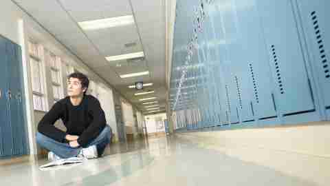 A teen boy sitting in a high school hallway, struggling to manage his workload