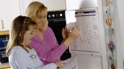 An ADHD coach helping a young girl schedule her assignments and find her possessions