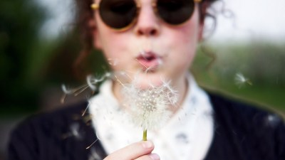 A woman is living her best life and blows an dandelion into the breeze.