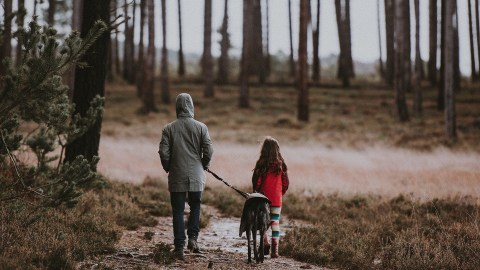 A girl with ADHD and her dad walk the dog outside as part of her nature therapy.