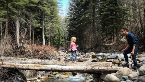 A dad with ADHD takes his daughter for a walk in the woods for nature therapy.