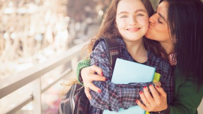 A mom hugs her daughter at school after explaining ADHD to teachers.