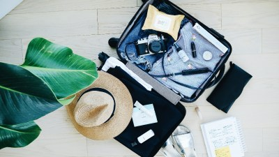 A woman uses a list of things to pack when travelling to fill her suitcase.