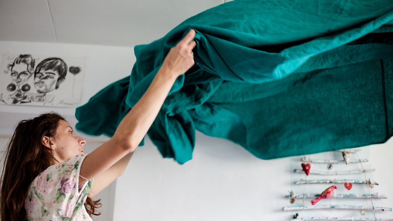 A woman with obsessive compulsive disorder (OCD) puts new sheets on her bed.
