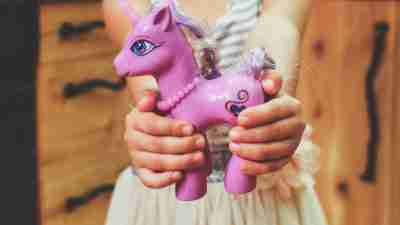 A girl holding a unicorn toy, which represents the beauty of being different with ADHD