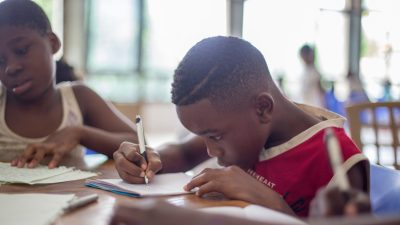 A young boy focuses on his schoolwork thanks to parent advocacy for his adhd