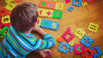 A boy with dyscalculia symptoms plays with numbers on the floor.