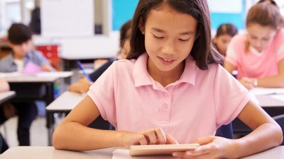 A girl uses a tablet to avoid having meltdowns at school.