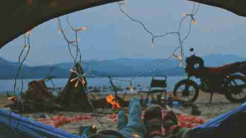 a couple camping near the beach represent the relationship goal of changing the atmosphere to remove yourself from a stresful environment