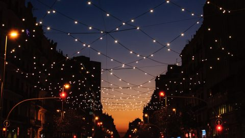 strings of lights over a city street represent working together instead of in opposition