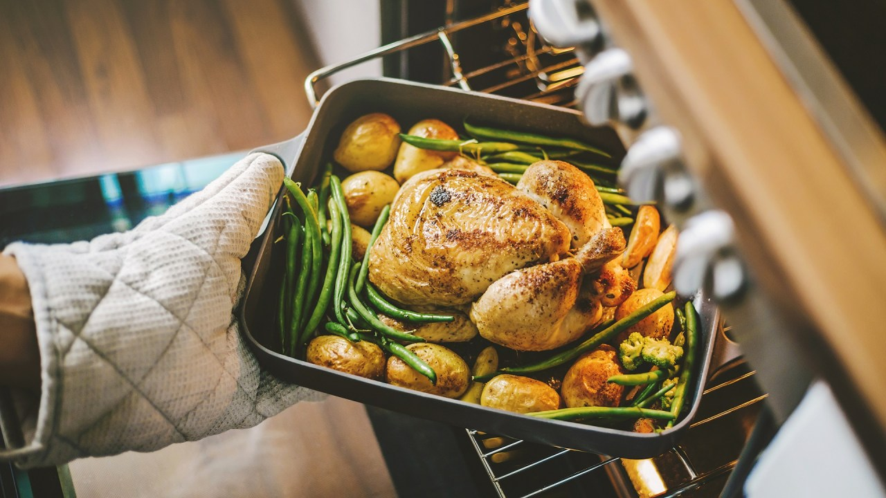 A woman roasts chicken and vegetables as part of her ADHD-friendly diet.