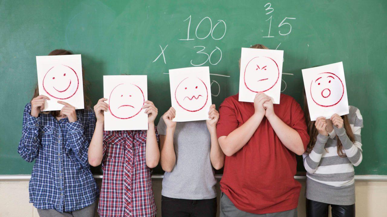 Students holding paper masks