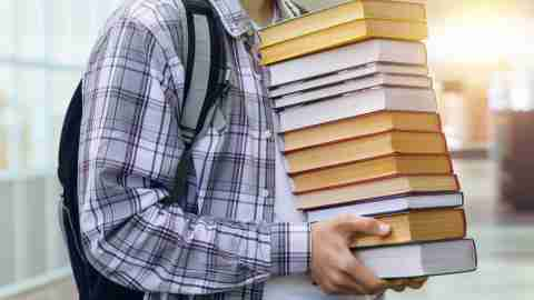 Student holds many textbooks. The concept of heavy research.