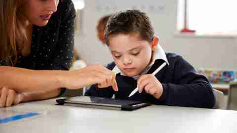 Young female teacher working with a Down syndrome schoolboy sitting at desk using a tablet computer in a primary school classroom, front view, close up