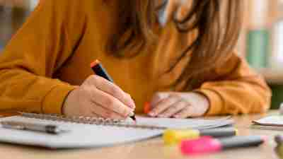 Young unrecognisable female college student in class, taking notes and using highlighter. Focused student in classroom. Authentic Education concept.