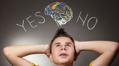 """A teenager with his hands to his head looking up at the words """"yes"""" and """"no"""" , deciding whether to tells others about his ADHD"""