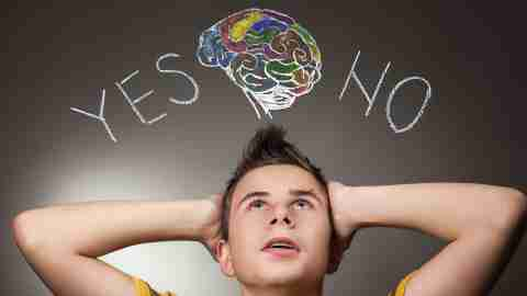 "A teenager with his hands to his head looking up at the words ""yes"" and ""no"" , deciding whether to tells others about his ADHD"