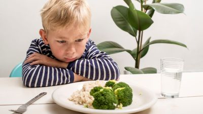 A picky eater frowning at his plate of vegetables. Coming up with healthy meals for picky eaters is easier than you think.