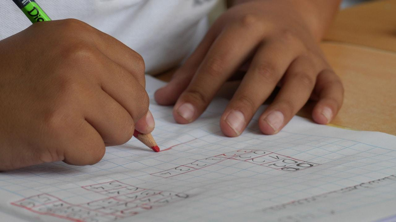 a boy with adhd works on his homework with accountability